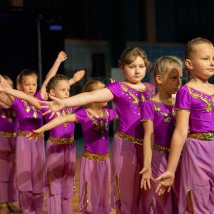 Osiem dziewczynek w strojach w kolorze fuksji stoi w rzędzie. Wyciągają w bok ręce.