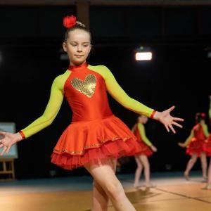 Dziewczynka w czerwonej krótkiej sukience z żółtymi rękawami, ze złotym sercem na piersi rozrzuca w bok ręce. W tle nieostre sylwetki koleżanek z zespołu.