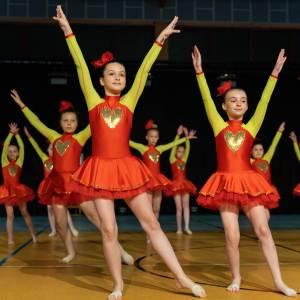 Dziewczynki w krótkich czerwonych sukienkach z żółtymi rękawami i złotym sercem na piersi unoszą w górę obie ręce. Lewą nogę wysuwają lekko w bok.