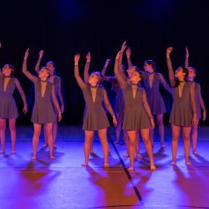 Grupa dziewczyn w szarych strojach unosi w górę prawe ręce. Wzrok mają skierowany w tym samym kierunku.