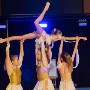 Trzy dziewczynki w biało-złotych strojach podnoszą w górę czwartą. Trzymają ją za lewą nogę i ręce. Dziewczynka leży płasko na brzuchu unosi w górę prawą nogę.