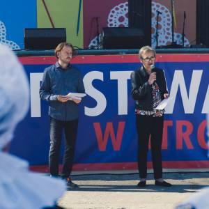 Przed sceną Krystian Weber i Krystyna Mikołajczak z mikrofonem. Na pierwszym planie dwa kobiece czepce.