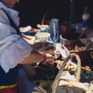 Kobieta smaruje smalcem pajdę chleba. Na stole chleb w koszyku i inne naczynia.