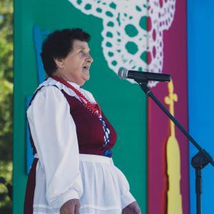 Kobieta przy mikrofonie. Ubrana w bordowy gorset, białą koszulę i fartuch. Na szyi czerwone korale.