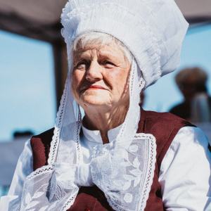 Zdjęcie portretowe. Starsza kobieta w białym czapcu z zawiązaną pod brodą kokardą.