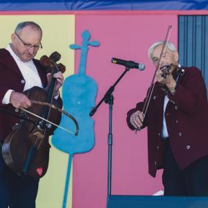 Na scenie dwaj mężczyźni w bordowych marynarkach. Jeden gra na basie, drugi na skrzypcach.