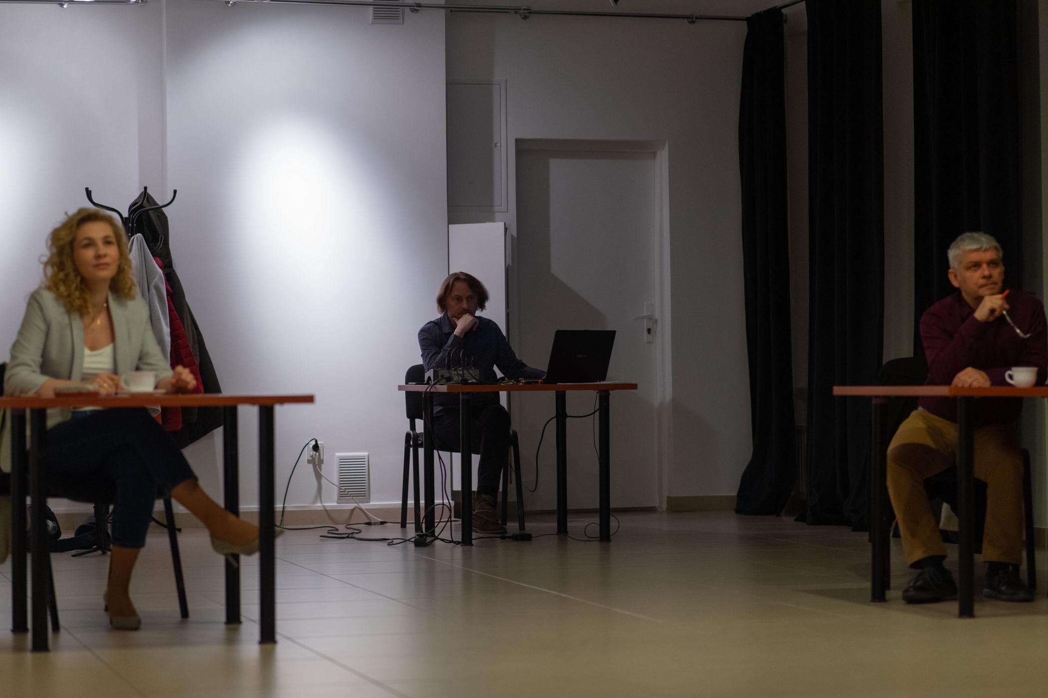 Zdjęcie przedstawia pomieszcenie, w nim trzy osoby, każda siedzi przy osobnym stoliku.