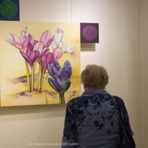 Na zdjęciu starsza kobieta ogląda obraz