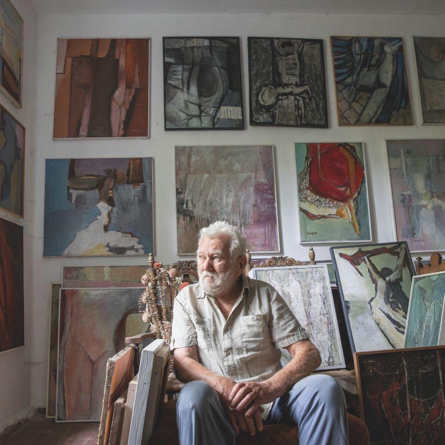 Na zdjęciu Jan Sznajder na tle swoich prac