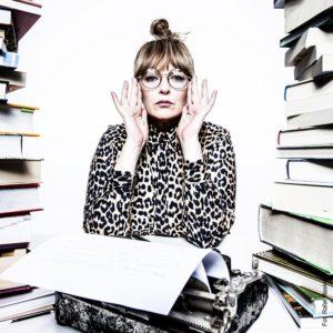 Kobieta w okólarach, za biórkiem, wśród książek