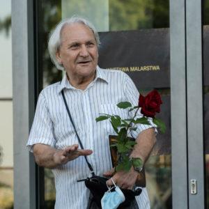 Na zdjęciu Kazimierz Białkowski z kwiatem, na tle drzwi do Centrum Kultury i Sztuki w Koninie