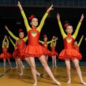 Dzieci w czerwono-żółtych strojach w układzie tanecznym na scenie