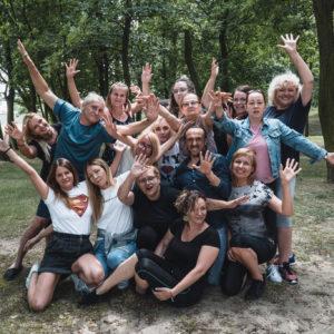 Grupa uczestników warszatów teatralnych. Zdjęcie wykonane w lesie.