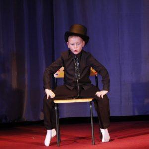 Scena. Chłopiec w cylindrze siedzi na krześle.e.
