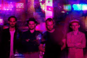 Na zdjęciu czterech mężczyzn stojących na tle kolorwej ściany