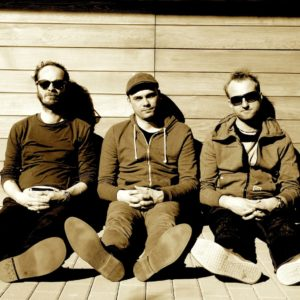 Na zdjęciu trzech mężczyzn siedzi oparty o drewnianą ścianę