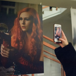 dziewczyna w maseczce wykonuje telefonem zdjcie wystawy fotograficznej