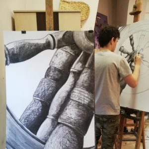 Pracownia plastyczna. Na peirwszym planie obraz na sztaludze, na drugim planie młody mężczyzna maluje obraz.