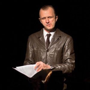 Mężczyzna w skórzanej marynarce, z dokumentami w dłoni