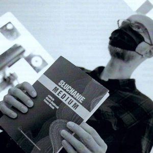 Mężczyzna prezentuje w dłoniach okładkę książki