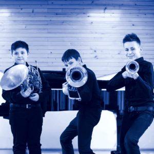 trzech chłopców z instrumentami dętymi